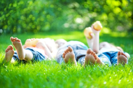 Children feet in green grass